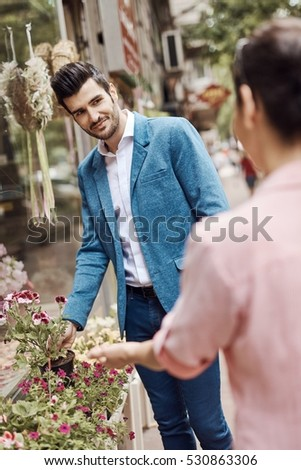Handsome young man buying flowers at florist, smiling.