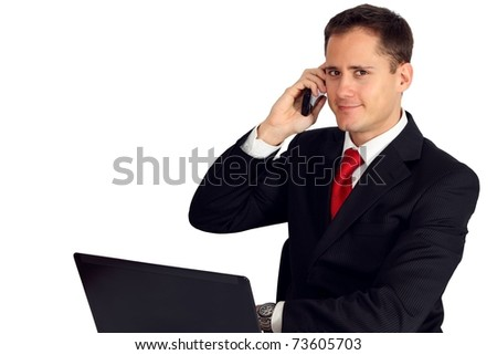 Handsome young man by his laptop making a call - stock photo