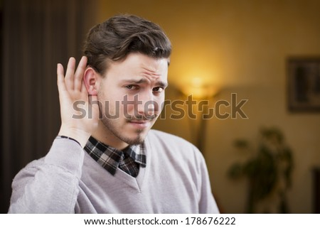 Handsome young man can't hear, putting hand around his ear. Indoors shot inside a house - stock photo