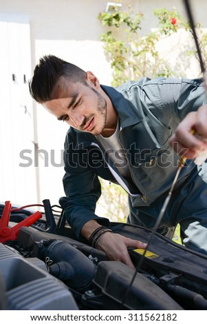 handsome young man car mechanic checking a car engine breakdown outdoor  - stock photo