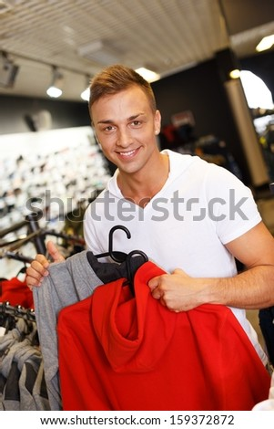 Handsome young man choosing sports wear in a sport outlet - stock photo