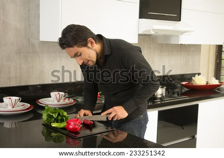 handsome young man cooking cutting vegetables in modern kitchen - stock photo