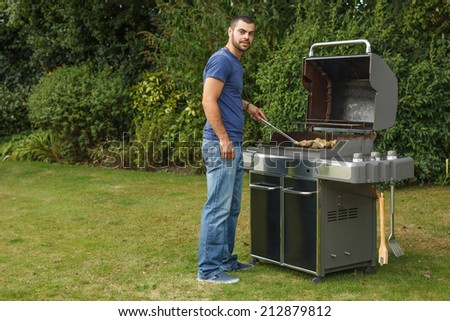 Handsome young man cooking meat for barbecue party in the garden