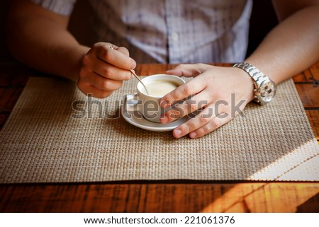 handsome young man drinking coffee. close up of guy sitting in cafe and holding cup - stock photo