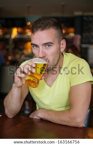 Handsome young man drinking light beer in a pub - stock photo