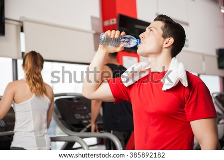 Handsome young man drinking water from a bottle and taking a break from exercising in a gym - stock photo