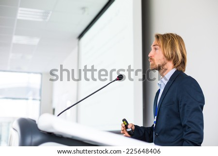 Handsome young man giving a speech at a conference - stock photo