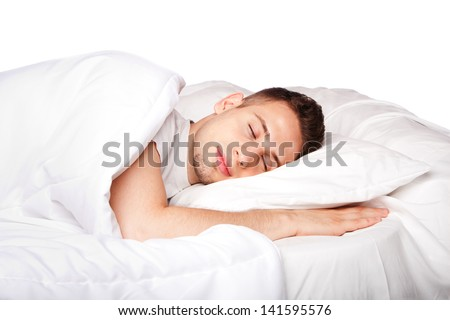 Handsome young man happily sleeping in white bed, isolated. - stock photo