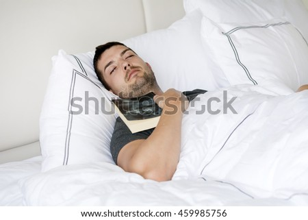 Handsome young man happily sleeping in white bed with book in the hands
