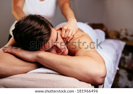 Handsome young man having his back massaged - stock photo