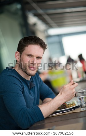 handsome young man having lunch in a restaurant outdoor