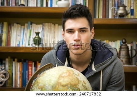 Handsome young man holding a globe indoors at home looking at the camera in front of a bookcase filled with books in a conceptual image - stock photo