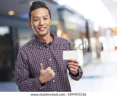 Handsome young man holding an empty visit card - stock photo