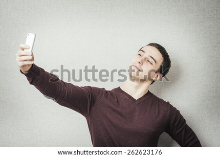 Handsome young man holding camera and making selfie and smiling while standing against grey background - stock photo