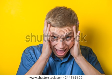 Handsome young man holding his hands behind his head and screams. Close portrait. Gesture. Isolated yellow background. photo - stock photo