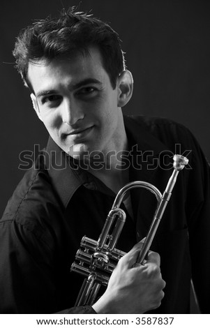 Handsome young man holding his trumpet wearing black
