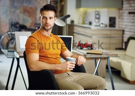 Handsome young man holding tea mug, daydreaming at home. - stock photo