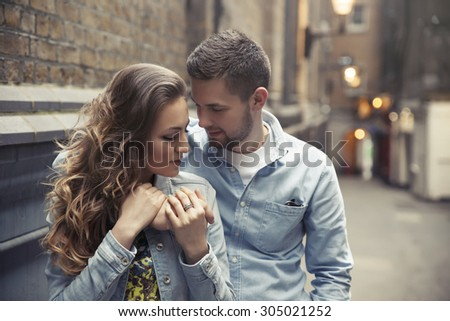 handsome young man hugging beautiful woman on street - stock photo
