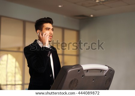 Handsome young man in a black suit, white shirt and tie talking on the phone on a treadmill in the gym - stock photo