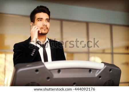 Handsome young man in a black suit, white shirt and tie talking on the phone on a treadmill in the gym