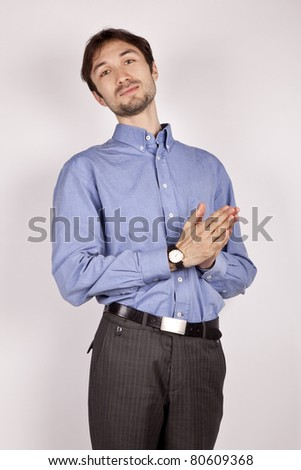handsome young man in a blue shirt stands with folded hands together as if planned something insidious - stock photo
