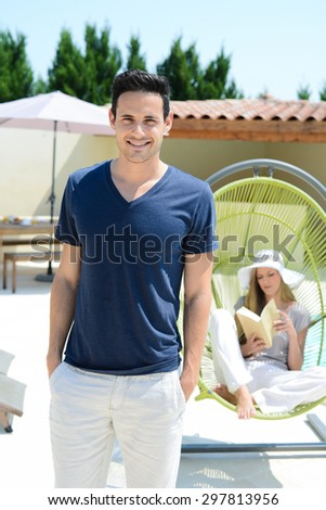 handsome young man in a pool terrace resort with girlfriend in background