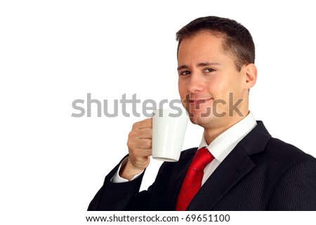 Handsome young man in a suit enjoying a cup of coffee, tea or chocolate - stock photo