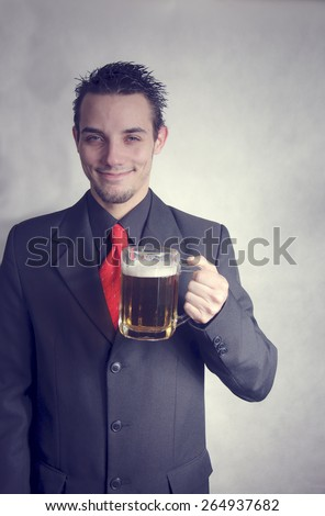 Handsome young man in a suit toasting with a beer