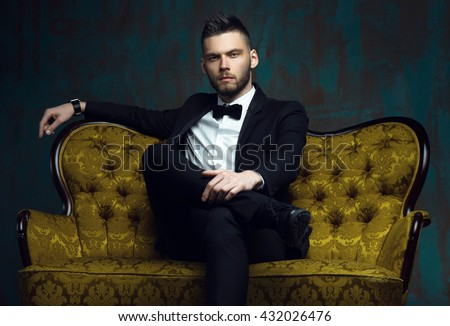 Handsome young man in a tuxedo looking at the camera. Fashionable Clothing. Clothing for the festive evening. Evening tuxedo. Fashion look - stock photo