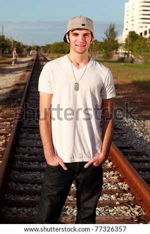 Handsome young man in a urban fashion pose along a railroad track. - stock photo