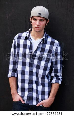 Handsome young man in a urban fashion pose in a downtown area. - stock photo