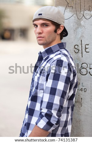 Handsome young man in an outdoor downtown urban fashion pose. - stock photo
