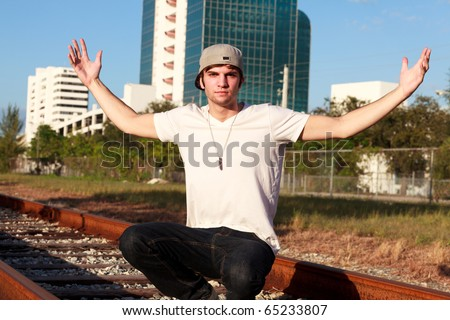 Handsome young man in an urban lifestyle pose along railroad tracks with his arms stretched out and wearing a baseball cap. - stock photo