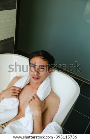 Handsome young man in bathtub at home having bath, washing body - stock photo