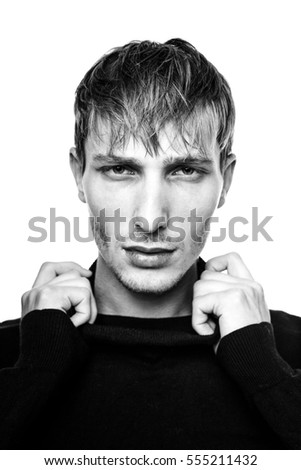 handsome young man in black jumper posing in studio, black and white photo