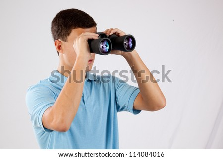 Handsome young man in blue shirt, looking through  a pare of binoculars