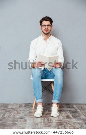 Handsome young man in glasses sitting on chair and reading a book over grey background