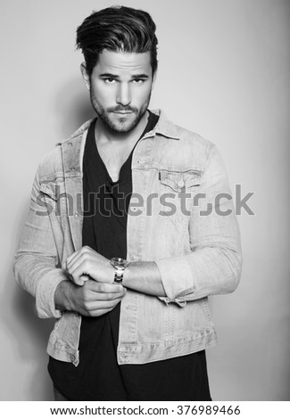 handsome young man in jeans jacket with wrist watch