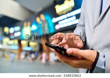 Handsome young man in shopping mall using mobile phone - stock photo