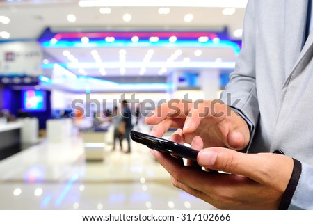 Handsome young man in shopping mall using mobile Phone. Selective focus on Mobile Phone in Hand. - stock photo