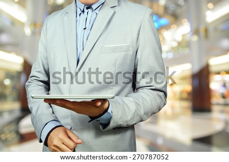 Handsome young man in shopping mall using mobile Tablet PC. Selective focus on Table and Hand. - stock photo