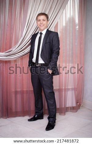 Handsome young man in  suit near window - stock photo
