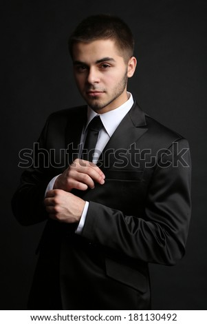 Handsome young man in suit on dark background - stock photo