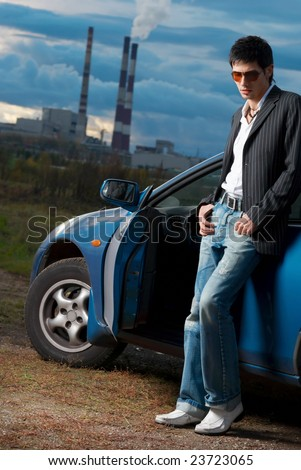 Handsome young man in sun glasses staying near blue car. Outdoor.
