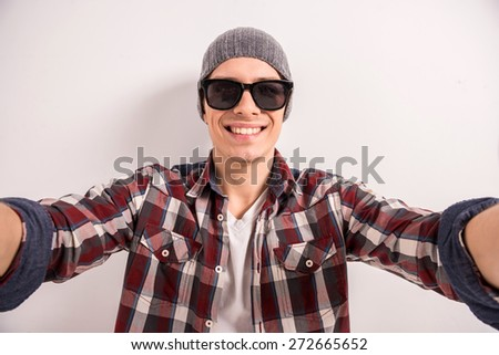Handsome young man in sunglasses is making selfie and smiling while standing grey background. - stock photo