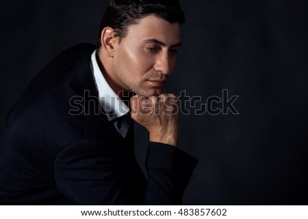 Handsome young man in the suit on black background