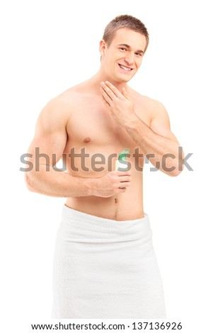 Handsome young man in towel applying skin cosmetics isolated on white background - stock photo