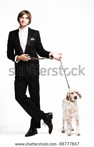 handsome  young  man in tuxedo and his dog, studio shot - stock photo