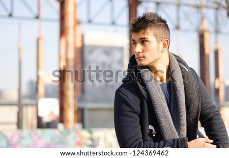 Handsome young man in urban or industrial setting looking to a side. Large copy-space. - stock photo