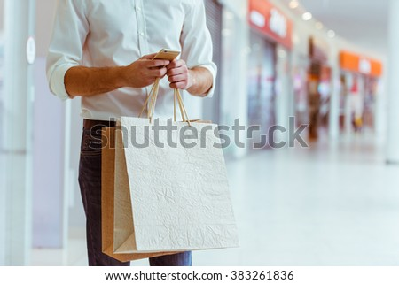 Handsome young man in white shirt holding shopping bags and using a smart phone while standing in mall, close-up